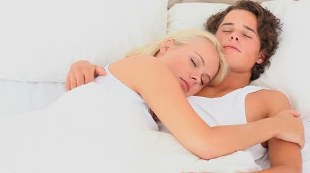 megölel : Cuddling couple in a bed in the bedroom Stock mozgókép