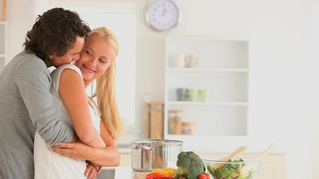 amantes : Happy couple cuddling  in the kitchen
