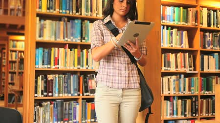 könyvtár : Young student working with a tablet in a library Stock mozgókép
