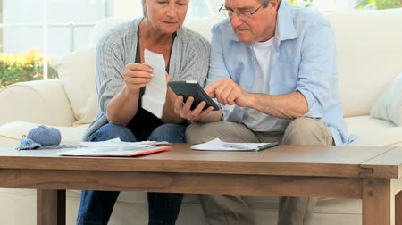 guy home : Mature couple calculating their bills at home