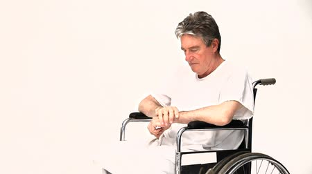 hemşirelik : Man in a wheelchair waiting for his nurse against a white background Stok Video