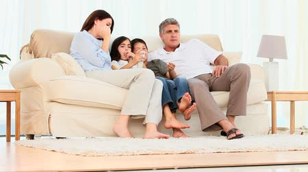 sitting room : Family watching tv on a couch Stock Footage