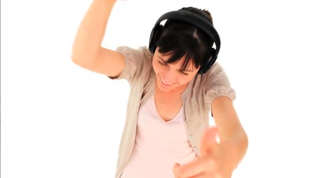 dans : Brunette girl listening to music isolated on a white background Stok Video