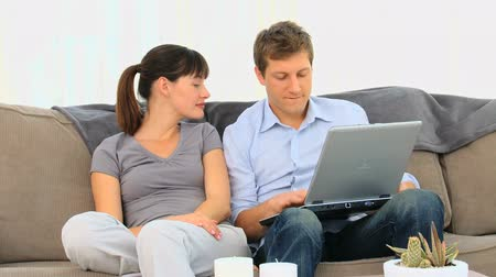 high def : Young couple using a laptop on a couch Stock Footage