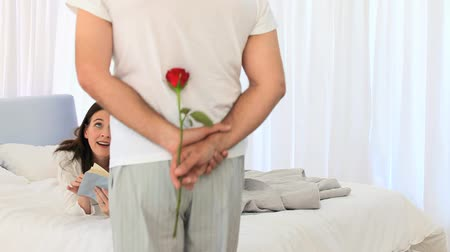 relação : Mature man offering a flower to his wife in the bedroom