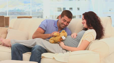 maci : Lovely couple playing with a teddy bear on their couch Stock mozgókép