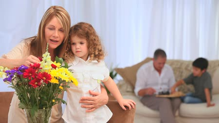 více barevné : Child smelling flowers with her grandmother in the living room