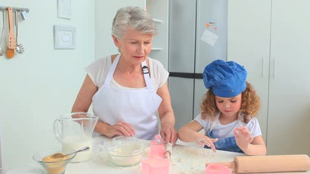 előkészítés : Grandmother and her grand daughter cooking together in the kitchen