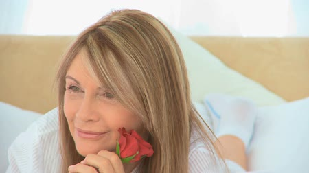 Роуз : Mature woman holding a rose in her bedroom Стоковые видеозаписи