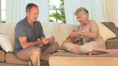 senior lifestyle : Elderly couple playing cards on the couch Stock Footage
