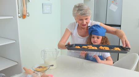 mutfak malzemesi : Grandmother and her grand daughter enjoying cookies that they just made Stok Video