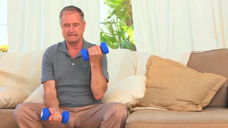 buty sportowe : Elderly man using dumbbells in the living room