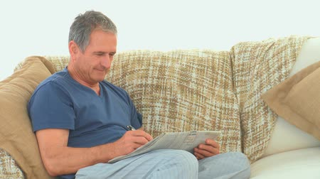 palavras cruzadas : Retired man doing cross words on his sofa Stock Footage