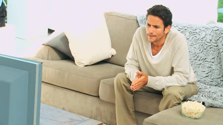 ideges : Handsome man getting nervous in front of the tv in his living room