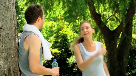 amantes : Athletic couple sharing a bottle of  water and a towel under a tree after jogging Vídeos