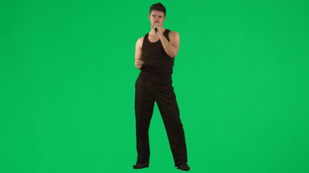 karaoke : Young man singing with a microphone footage against green screen