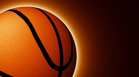 franczyza : Animation of a basket ball turning against black and orange background in high definition Wideo
