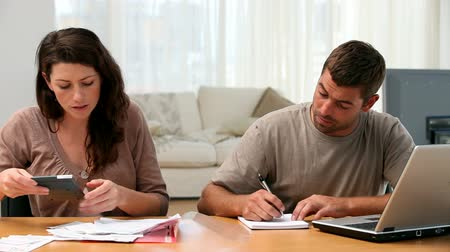 плата : Couple calculating their bills together in the living-room at home