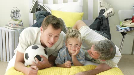 sziám : Grand farther and grandson watching football while lying on a bed
