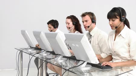 komputer : Business people working in a call centre against a white background
