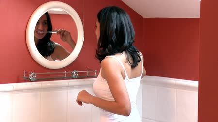 уборная : Brunette woman brushing her teeth in the bathroom
