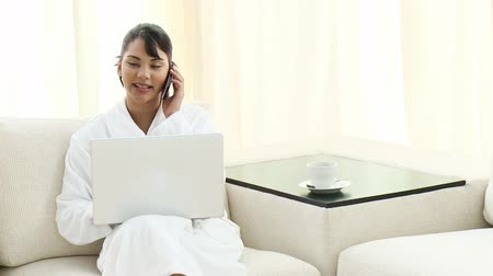 telefones : Young woman with a bathrobe using a laptop and talking on mobile in the living-room at home. Footage in high definition