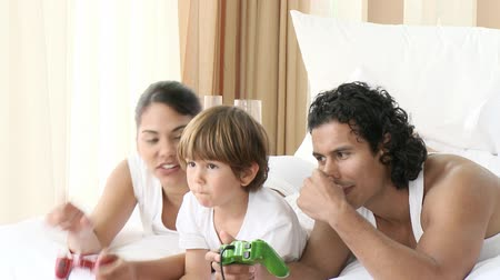 дичь : Happy family playing video games in bed. Footage in high definition