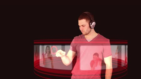 music show : A man with headphones on interacts with a 3d interface to find some good music Stock Footage