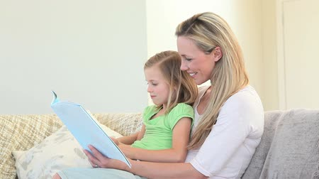 olvasás : A mother and daughter sit on the couch looking at a picture book Stock mozgókép