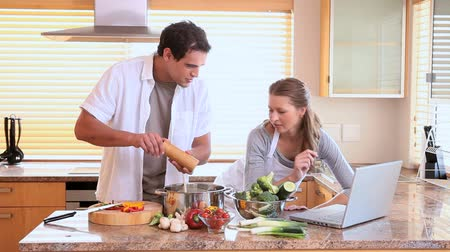 preparing food : Man and woman use the laptop for a reciepe while they are cooking in the kitchen Stock Footage