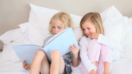 irmãos : Brother and sister sit together on the bed and read a book