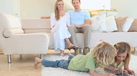 kanapa : Couple looking their children playing on the floor in the living room