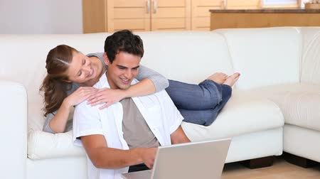 mężczyźni : Woman embracing her boyfriend using a laptop on a living room