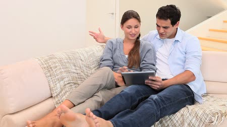 boso : Couple using a tablet computer while sitting in a living room