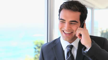 conversando : Smiling man in suit on the phone next to a window
