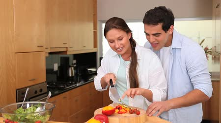 zakochana para : Man embracing his wife whos cooking in the kitchen