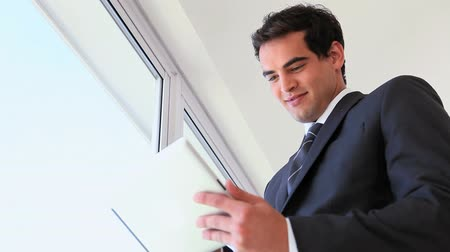 business man : Man in suit using a touchpad near a window Stock Footage