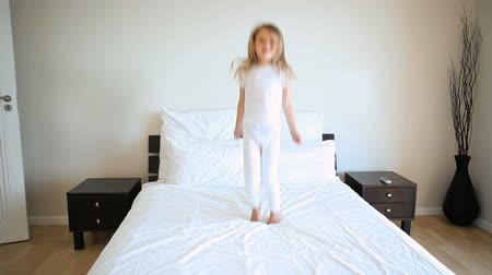 almofada : Blonde girl jumping on a bed