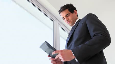 biznesmen : Businessman using a calculator while standing