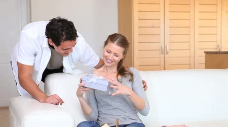 подарок : Man giving a gift in a  box to his girlfriend in the living room Стоковые видеозаписи