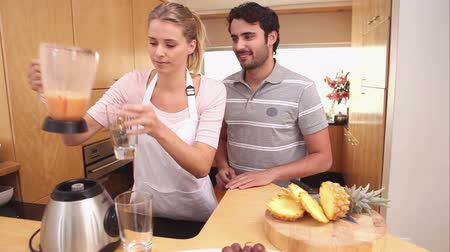 ananas : Lady giving a smoothier to her boyfriend in the kitchen Stok Video