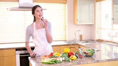 comer : Young woman preparing a salad in her kitchen