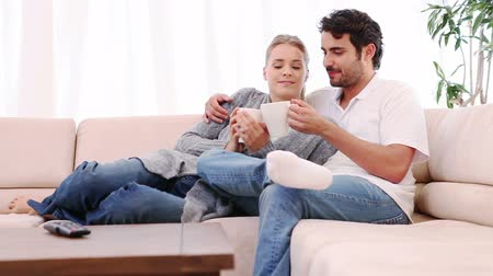 ül : Couple talking while sitting with a cup of coffee in their living room Stock mozgókép