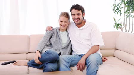 szófa : Couple sitting on a sofa while watching a movie in their living room
