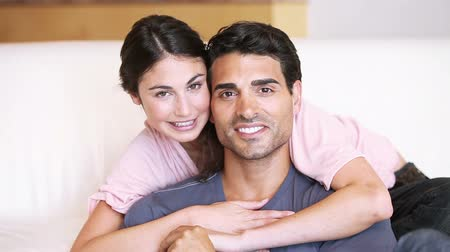namorado : Young woman hugging her boyfriend in her living room Vídeos