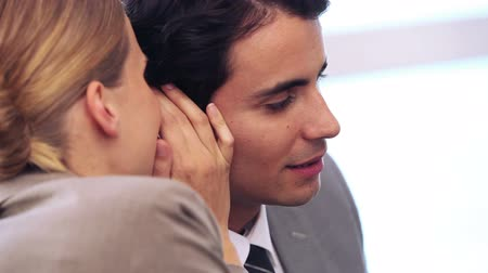 kulaklar : Businesswoman telling a secret to her colleague in a bright office Stok Video