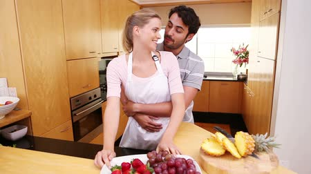 ananas : Smiling couple eating fruits in the kitchen Stok Video