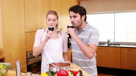 kötény : Young couple celebrating with wine in the kitchen Stock mozgókép