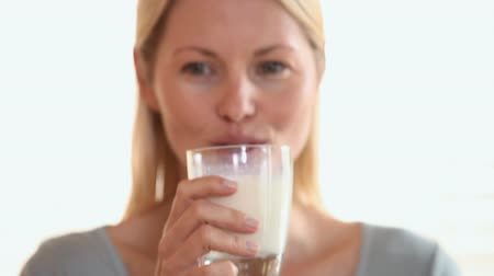 içme : Woman lifts a glass of milk off a table and takes a drink