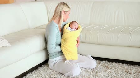 cobertor : Woman kissing and rocking a baby in her arms in a living room
